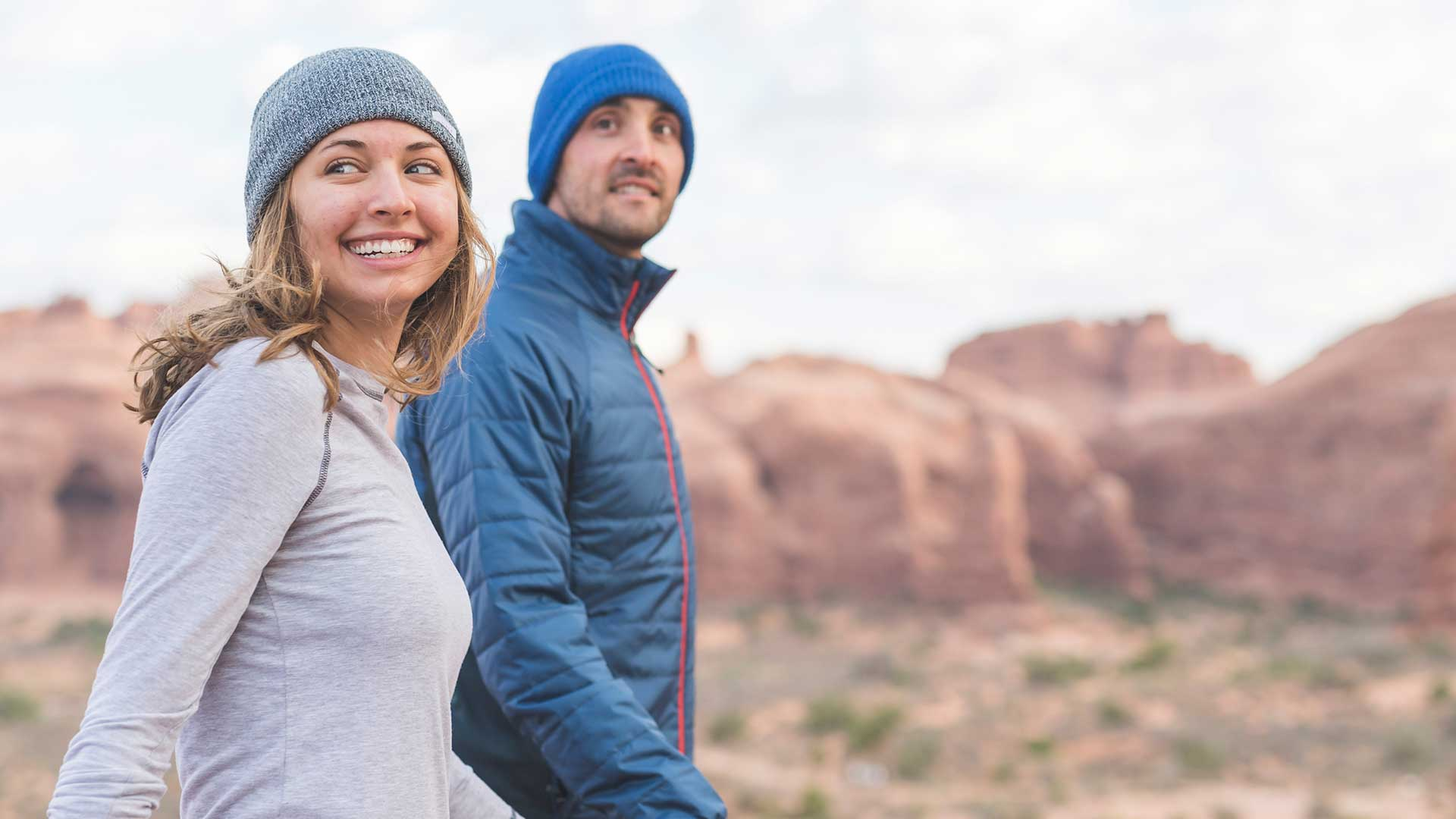 young couple smiling and holding hands hiking in zions national park