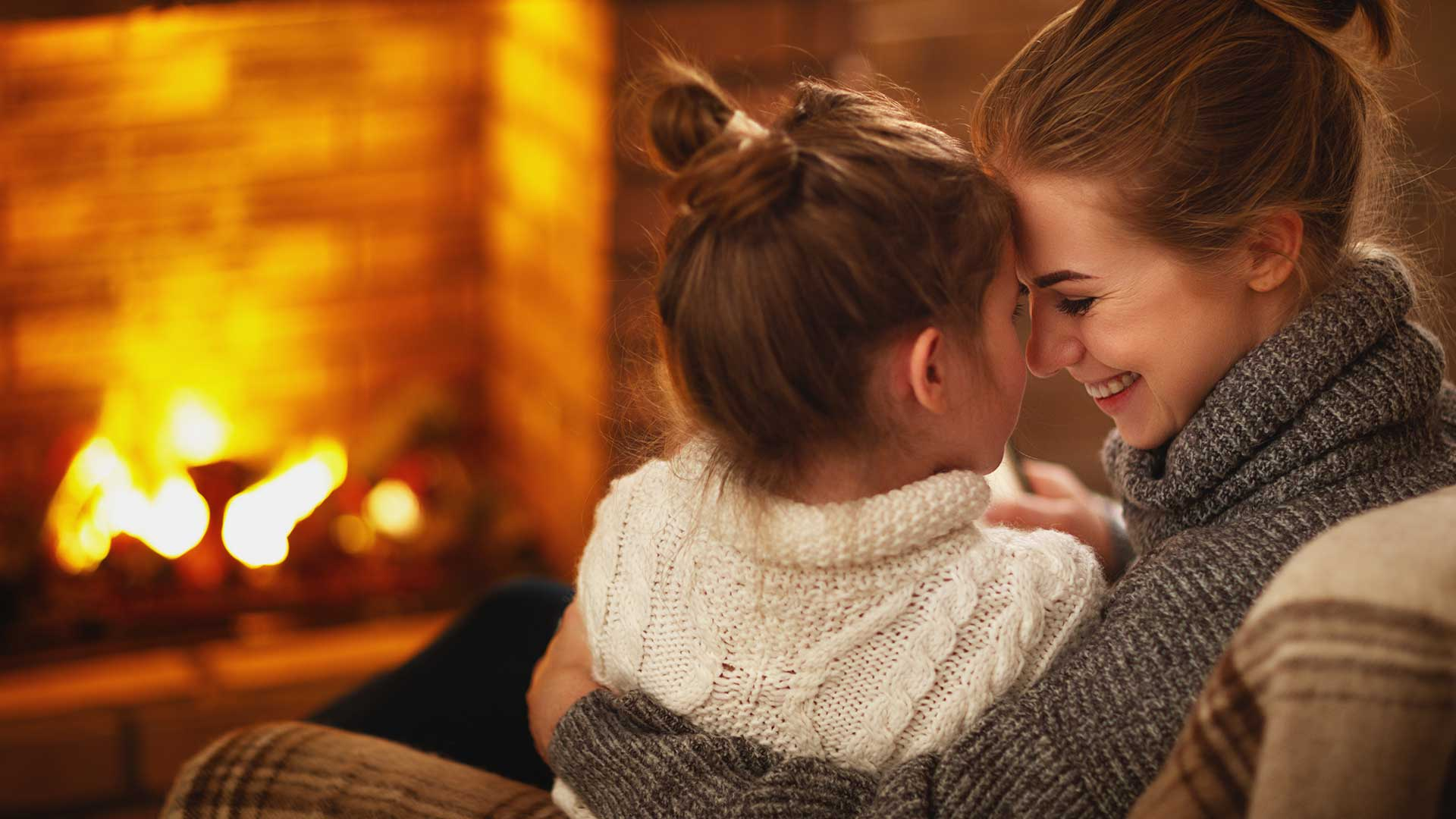 Mom and daughter cuddling on couch in front of cozy fire.