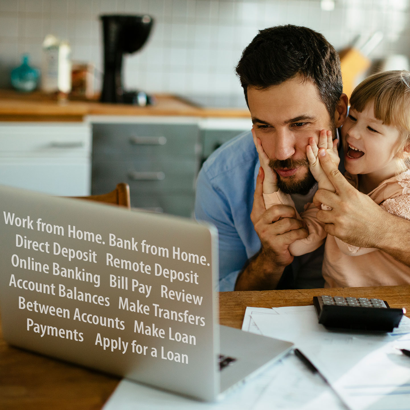 Man doing home banking on his laptop while daughter plays with his face.