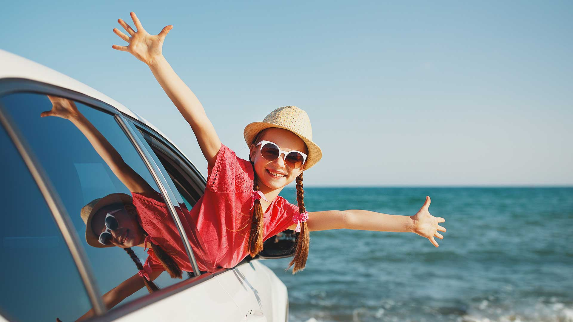 young girl hanging out passenger window of family car parked at the beach