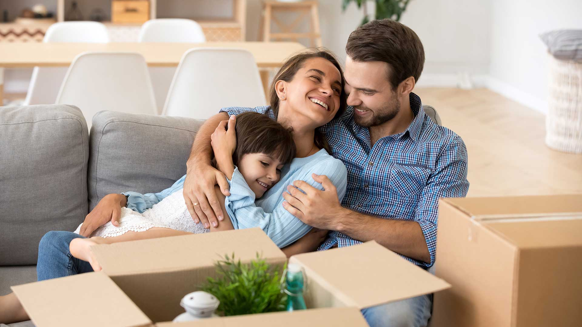 mom and dad hugging daughter on couch in new home surrounded by moving boxes
