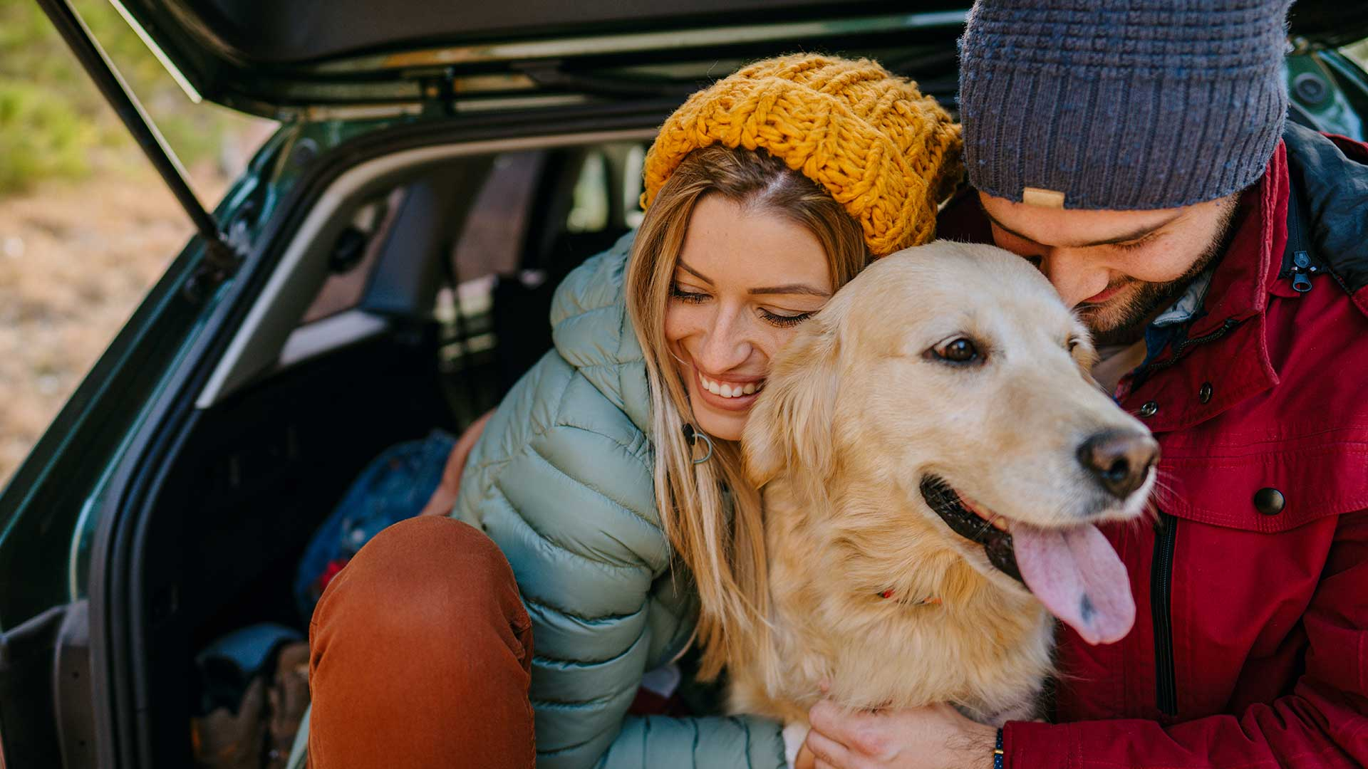 A young couple hugging their dog in the back of their SUV they financed with the best rates in Southeastern Utah at Desert Rivers Credit Union.